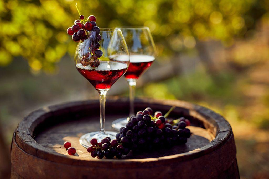 Două pahare de vin roșu pe un butoi de lemn